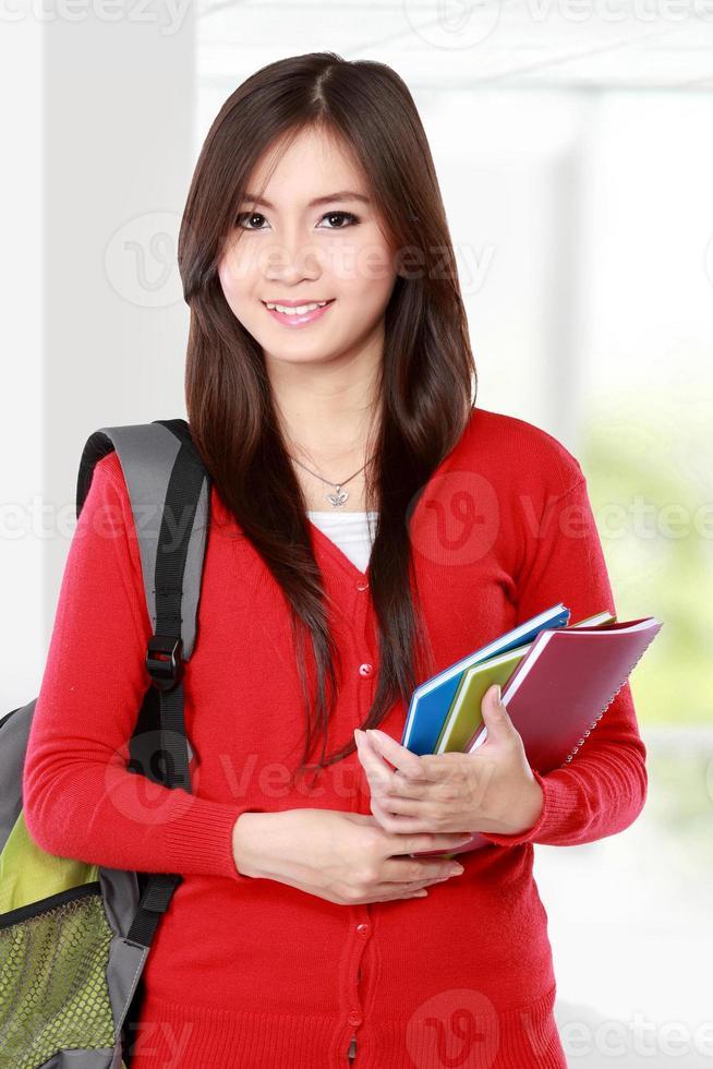 bela aluna com livros sorrindo foto