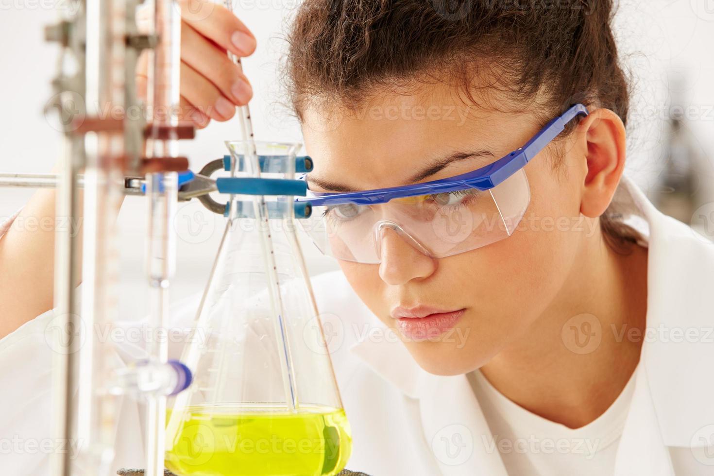 cientista feminina estudando líquido no balão foto