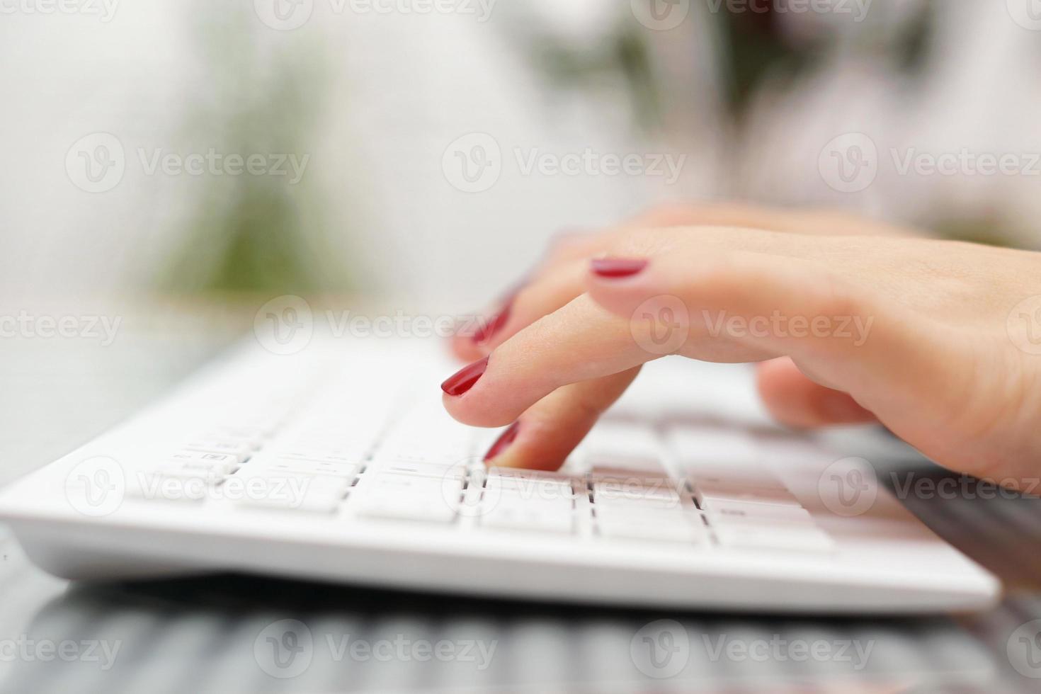 femininos dedos digitando no teclado branco foto