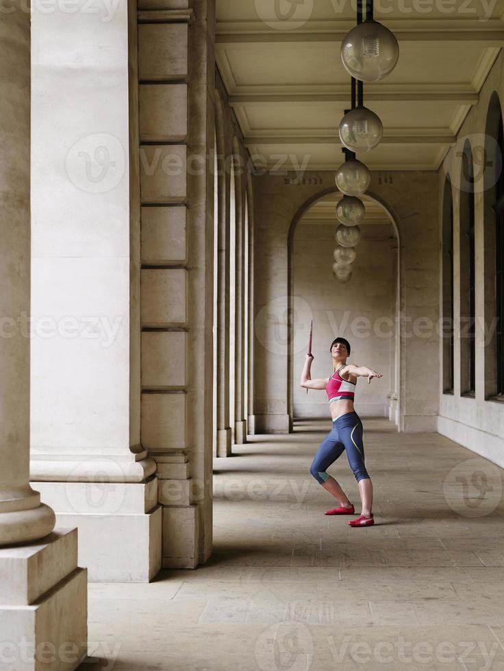 atleta feminina jogando dardo no pórtico foto