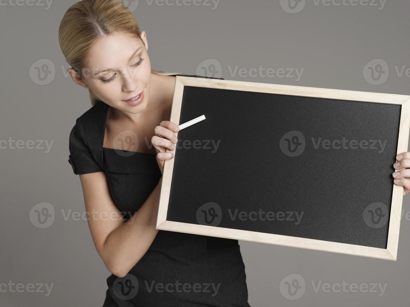 professora com quadro-negro e giz foto