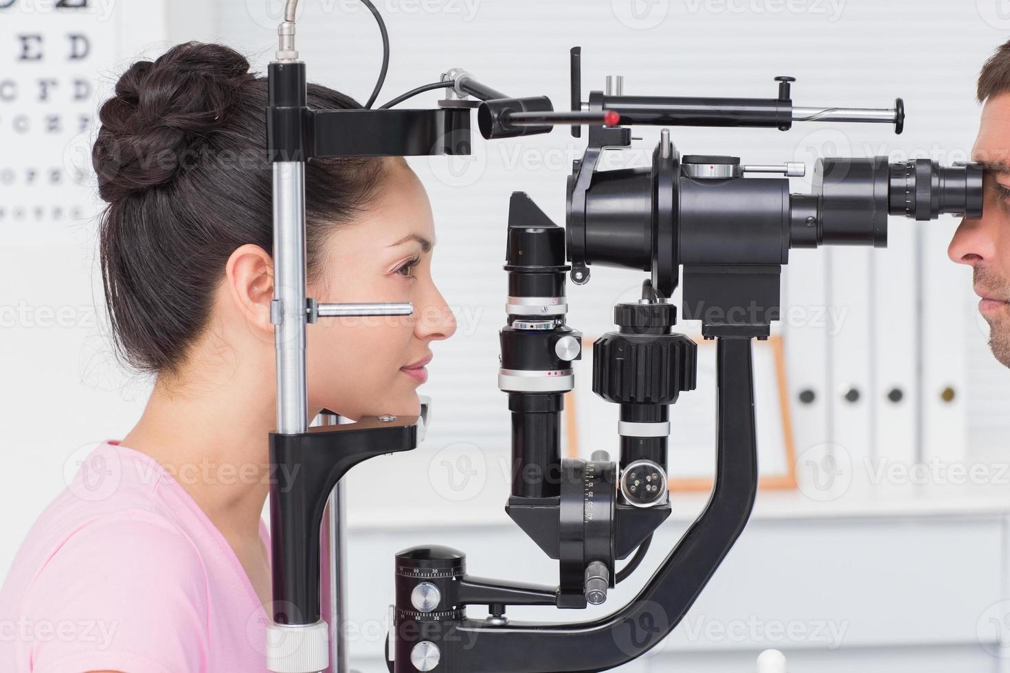paciente do sexo feminino sendo examinada pelo oculista foto