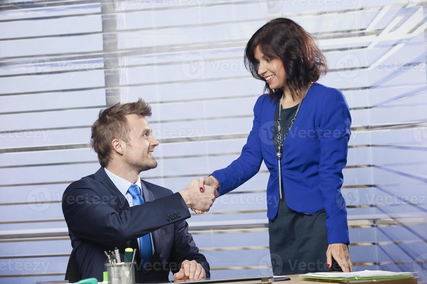 parceiros de negócios masculinos e femininos, apertando as mãos foto