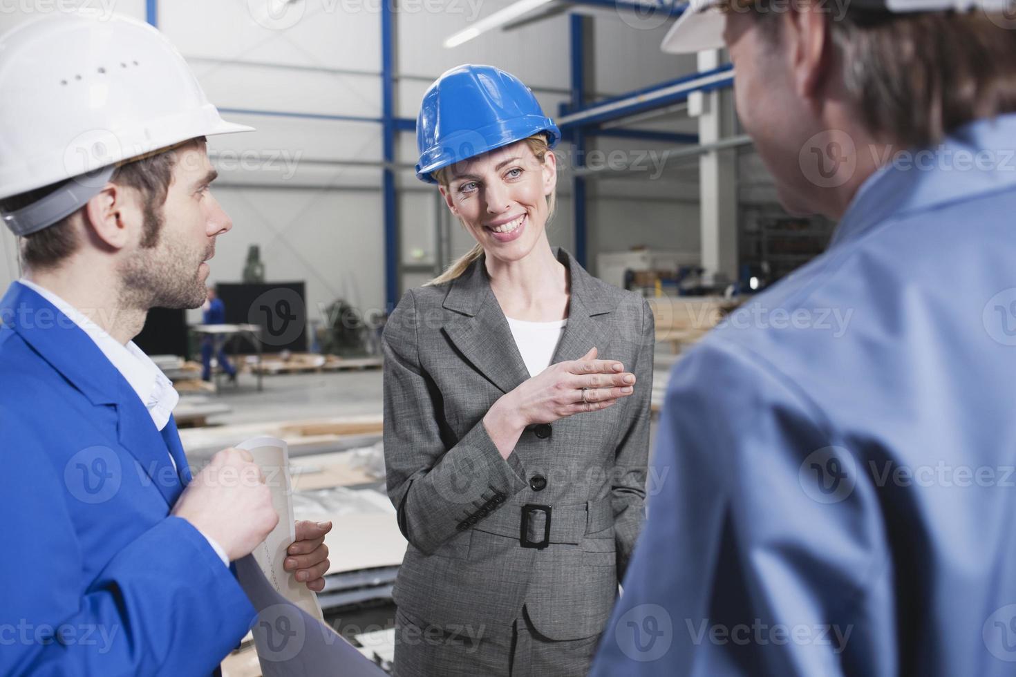 arquiteto feminino e capatazes no salão industrial foto