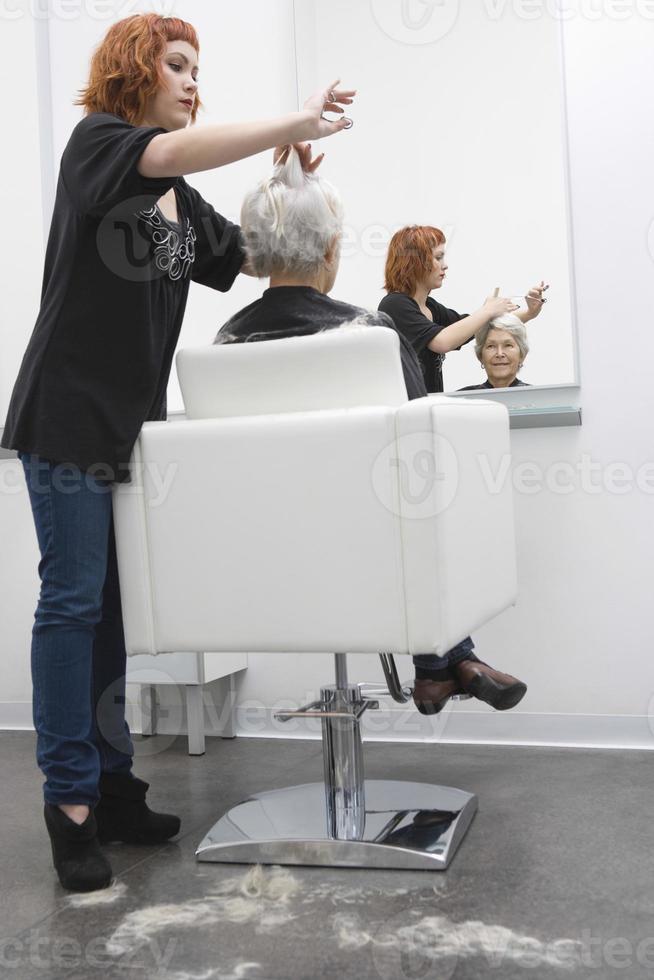 cabeleireiro feminino, dando o corte de cabelo para mulher sênior foto