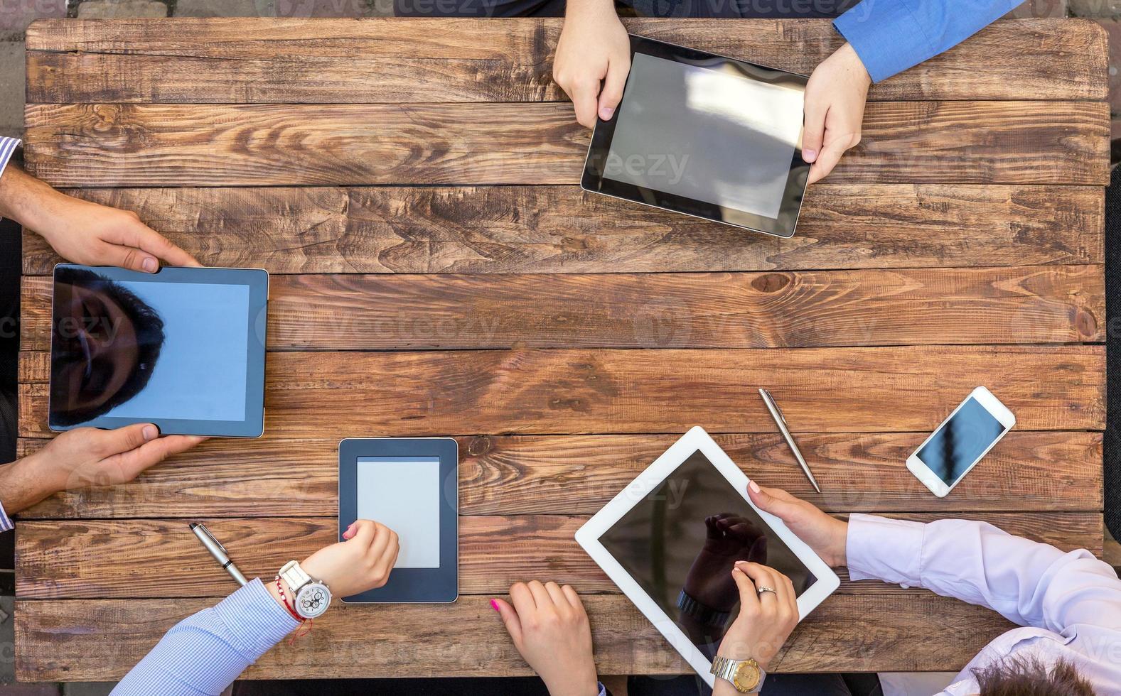 braços masculinos e femininos com gadgets Digitas foto
