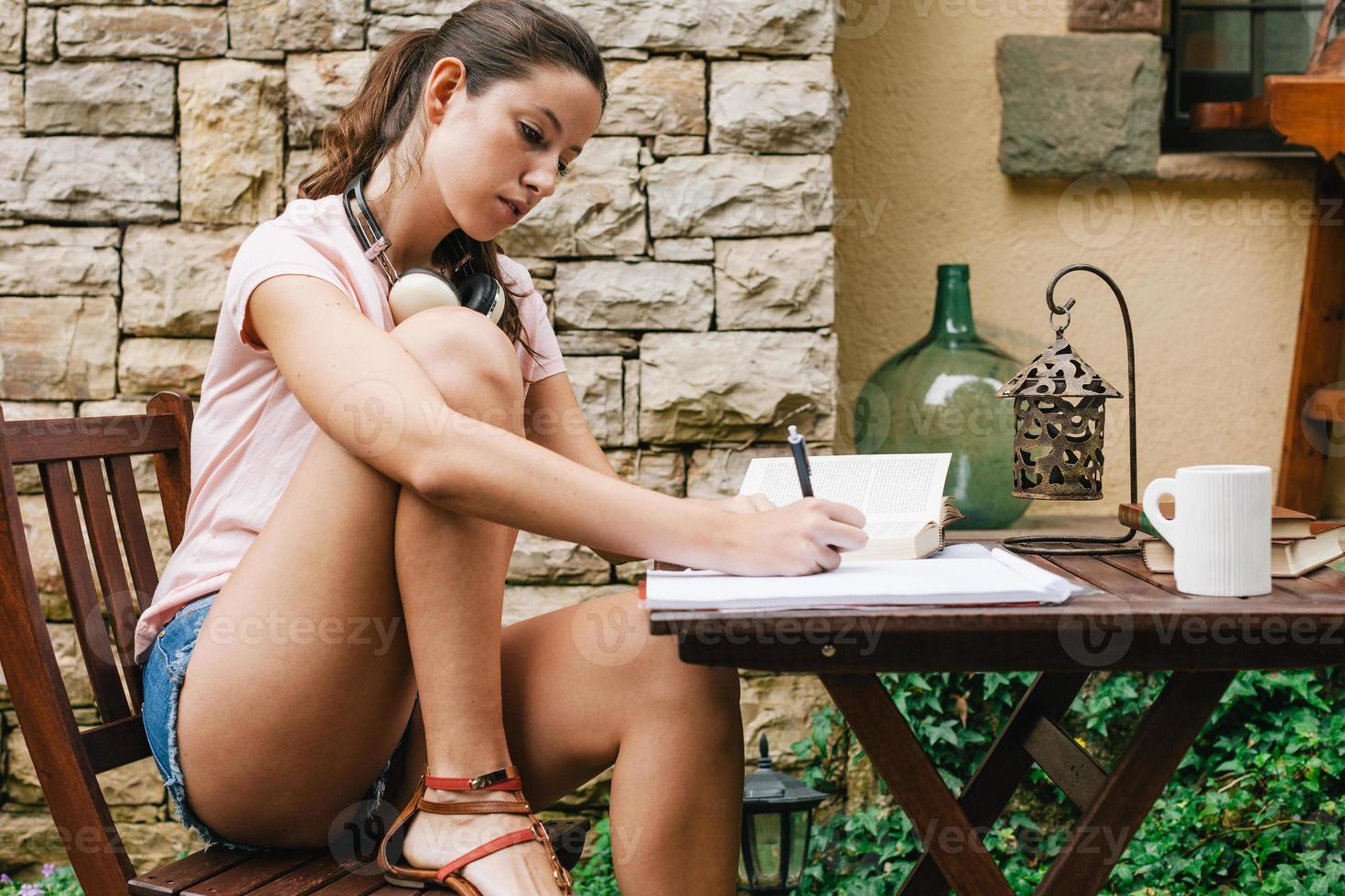 jovem fêmea bonita sentado lá fora e estudando muito. foto