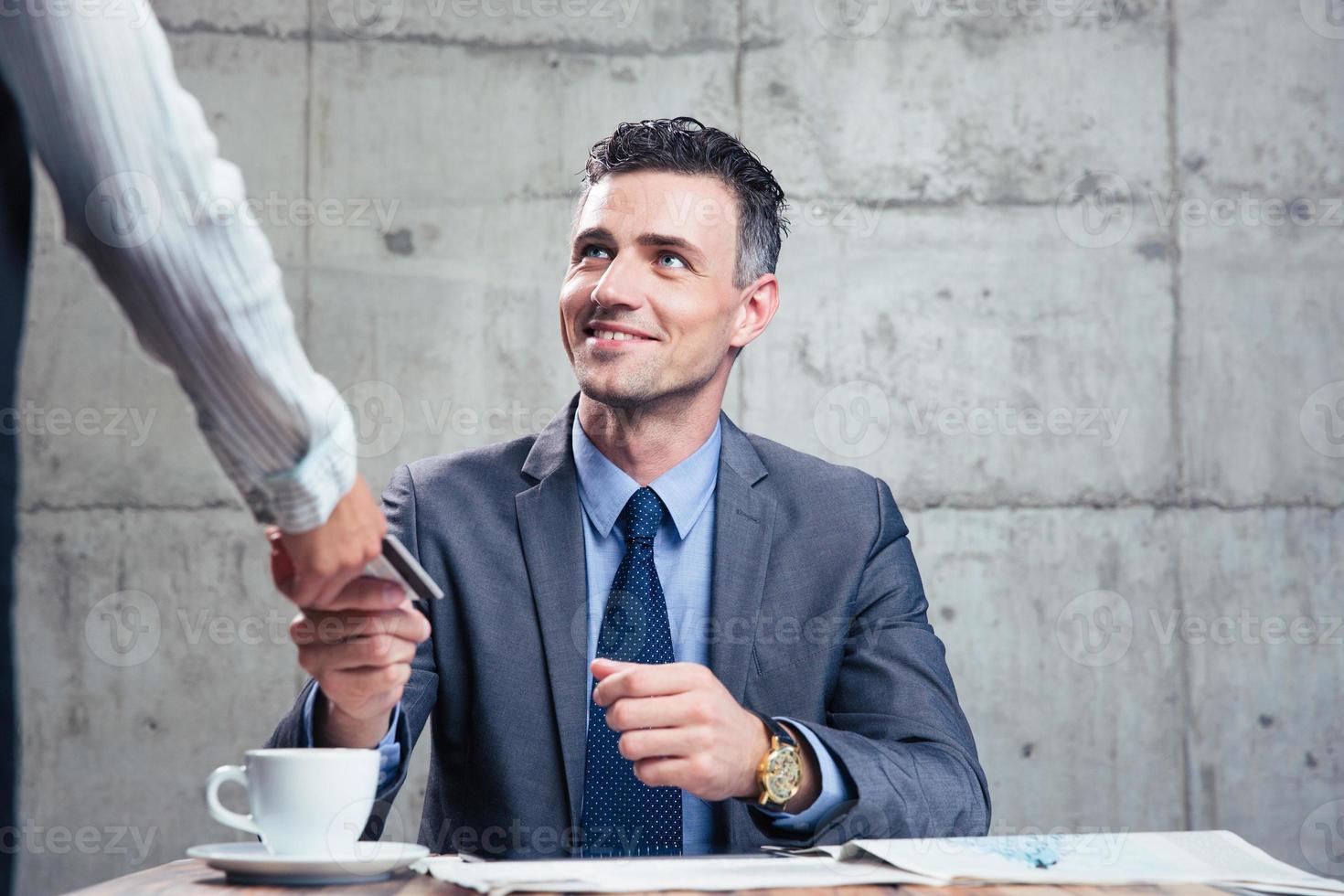 homem dando cartão bancário para garçom feminino foto
