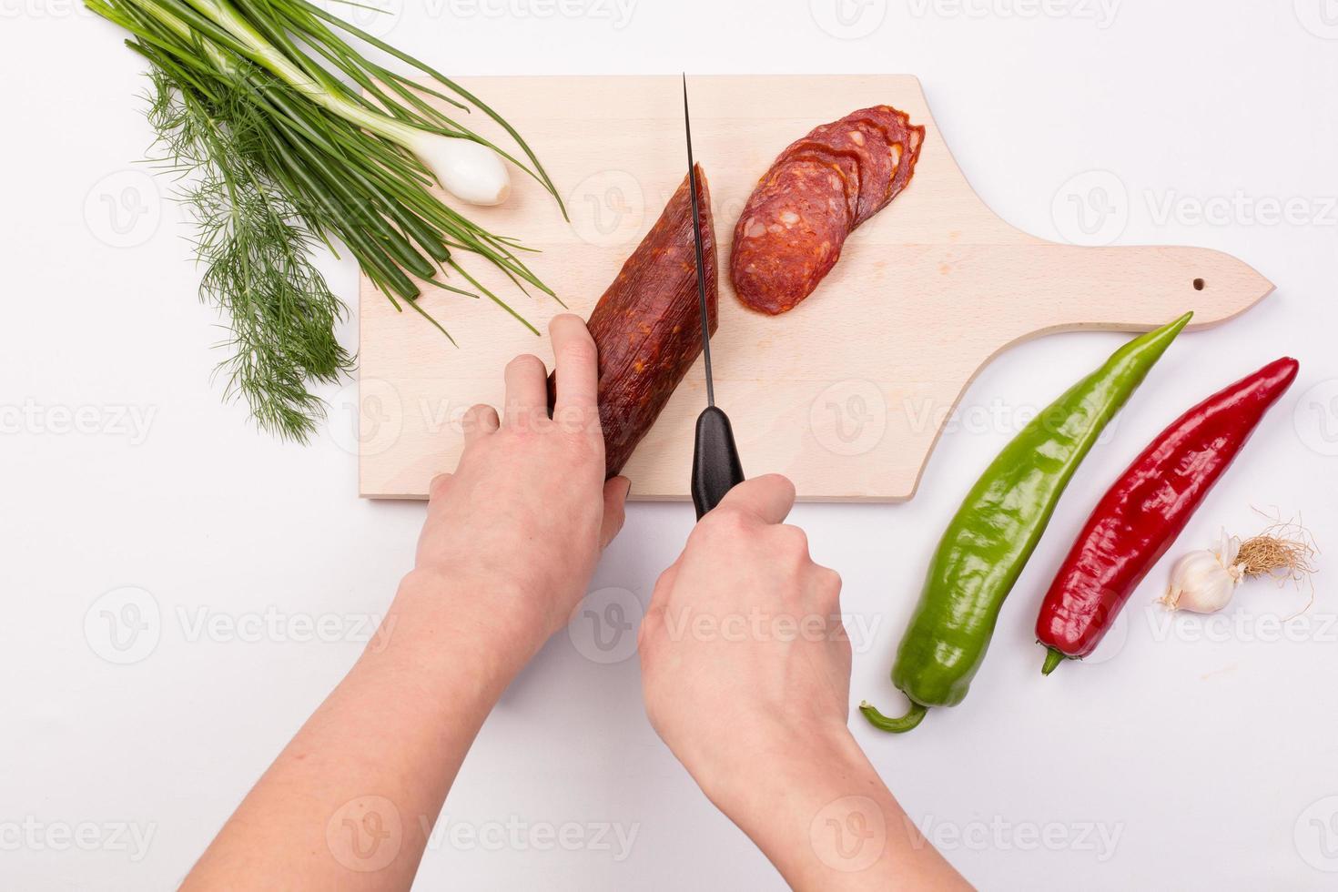 mãos femininas, corte fatias de linguiça vermelha foto