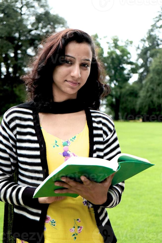 feliz aluna indiana em pé na grama. foto