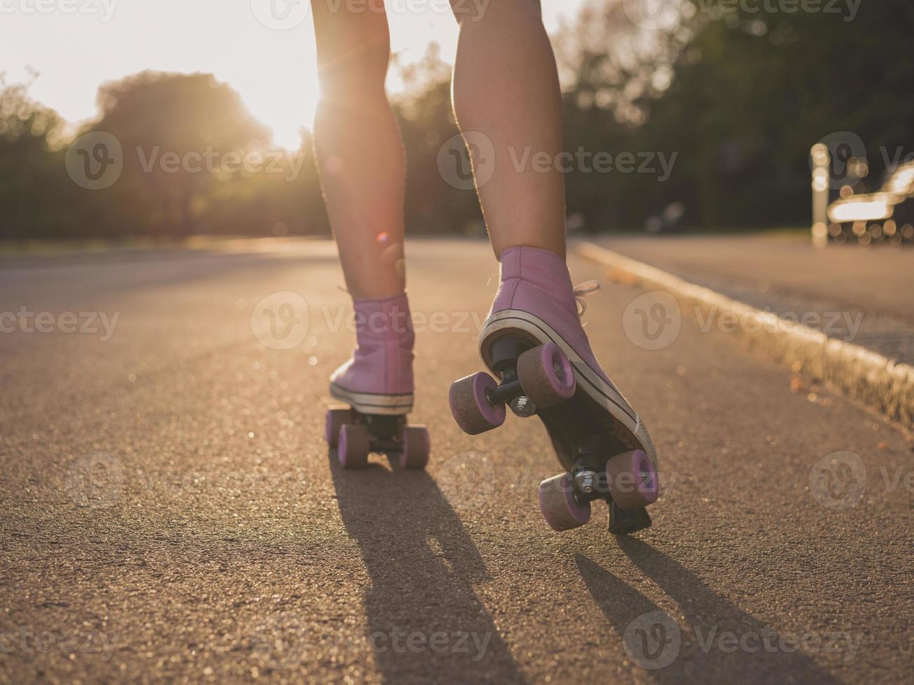 pernas de mulher jovem, andar de patins no parque foto