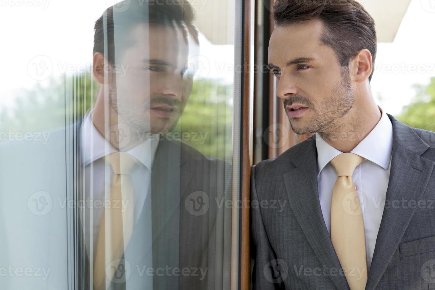 empresário pensativo, apoiando-se na porta de vidro foto