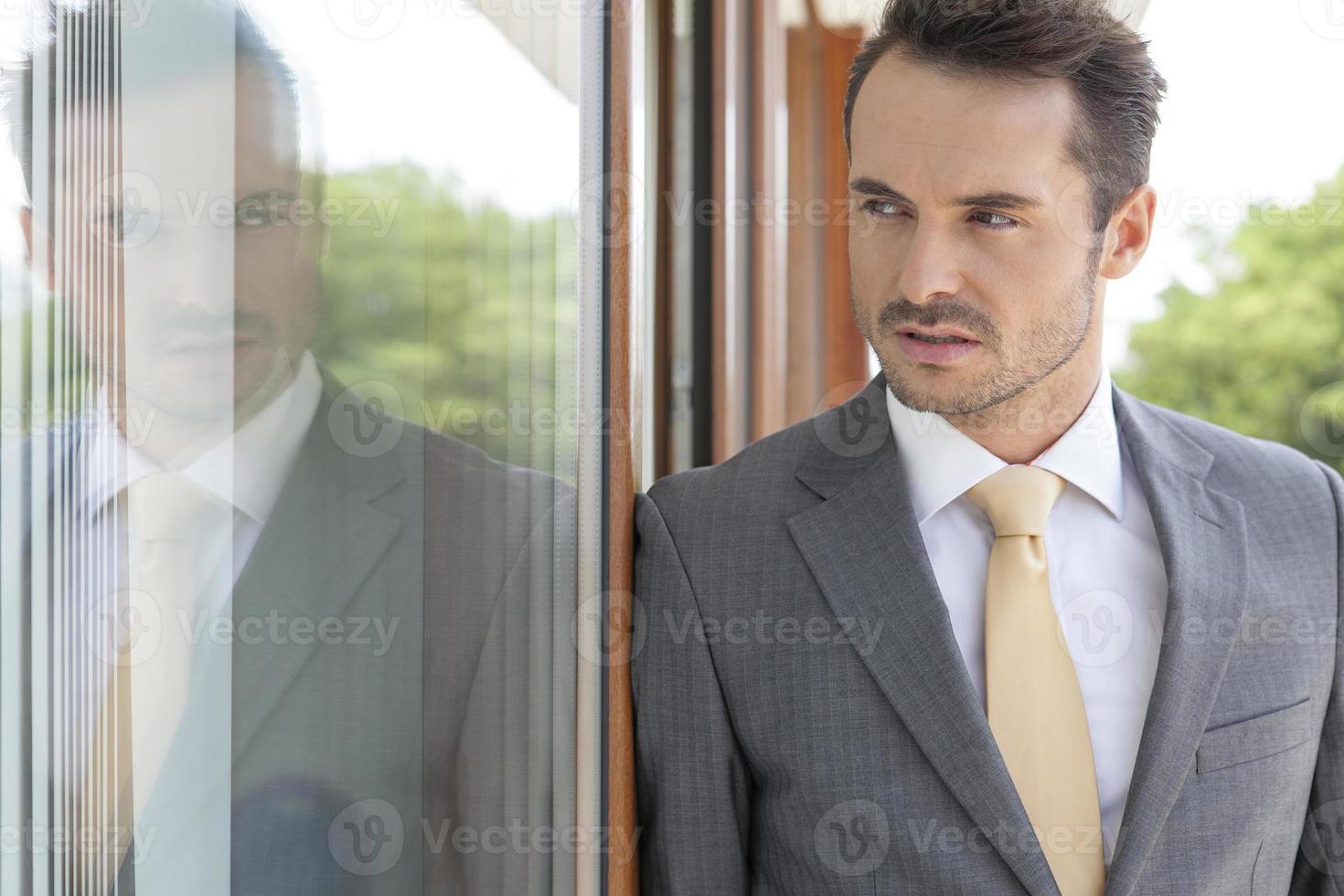empresário, olhando para longe enquanto encostado na porta de vidro foto