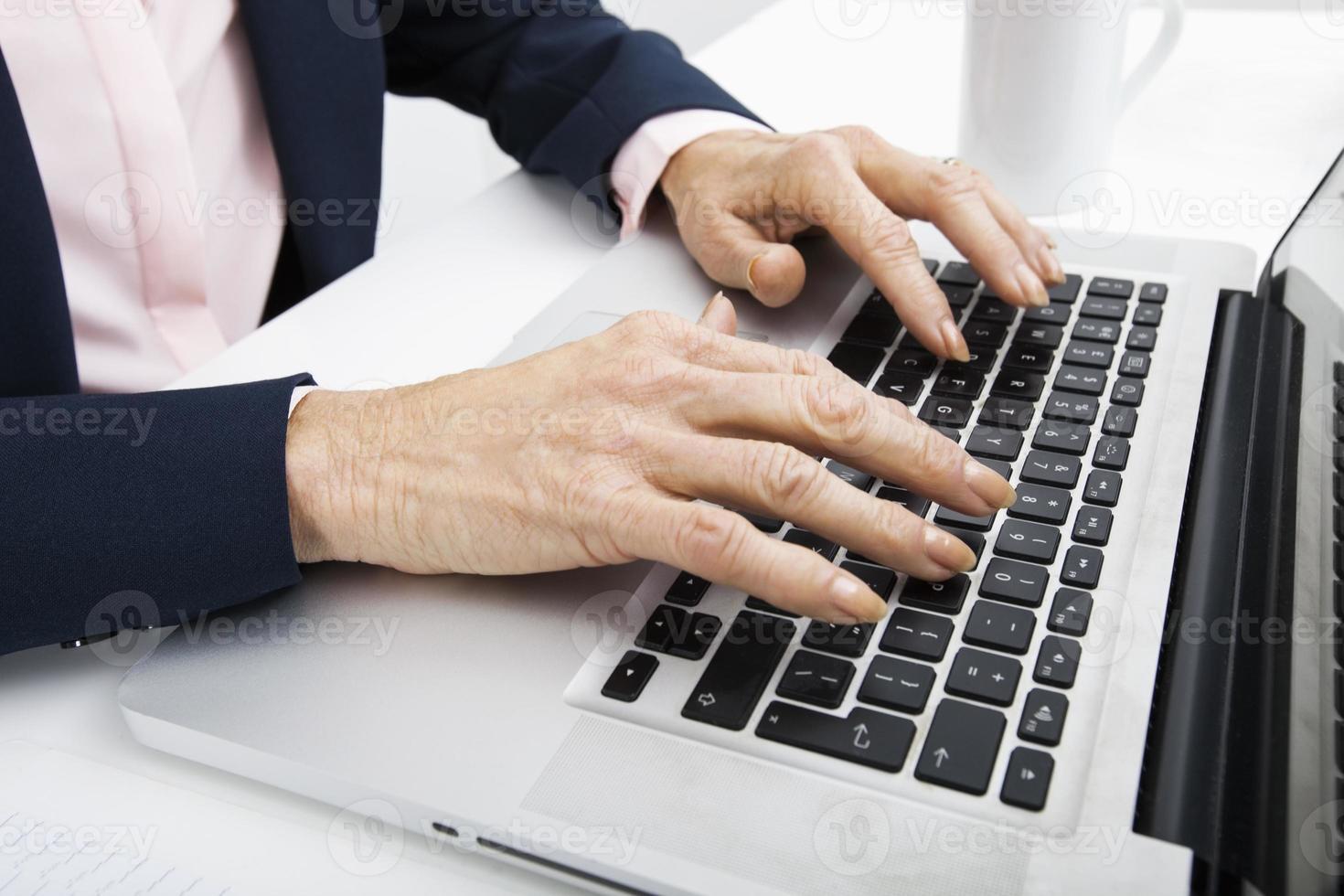 imagem recortada de empresária sênior digitando no laptop foto