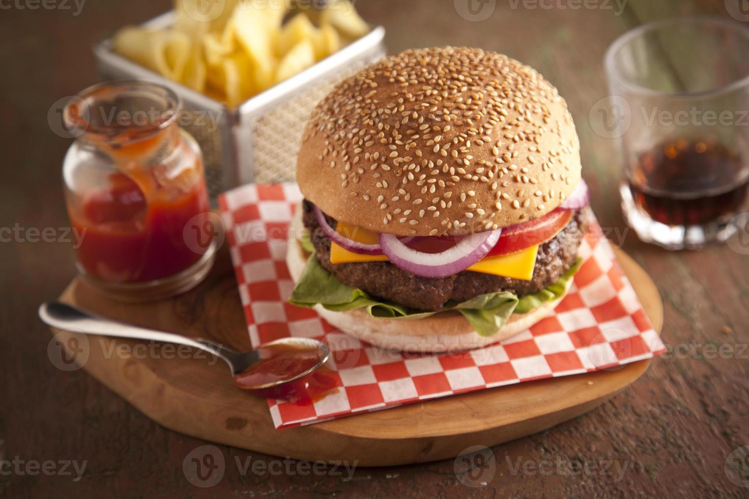 clássico cheeseburger cebola, tomate e picles pão de gergelim. foto