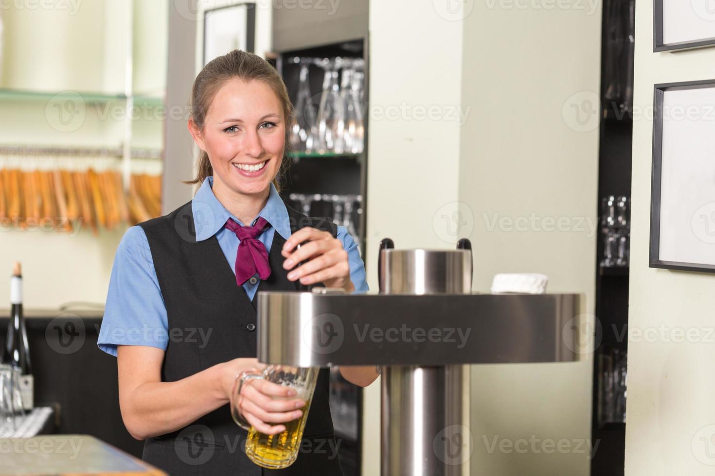 garçom no bar ou pub, enchendo o copo com cerveja foto