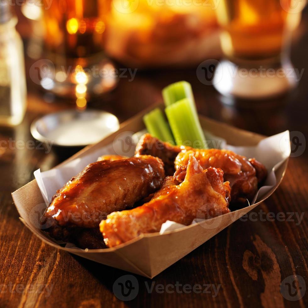 asas de frango de churrasco na bandeja descartável foto