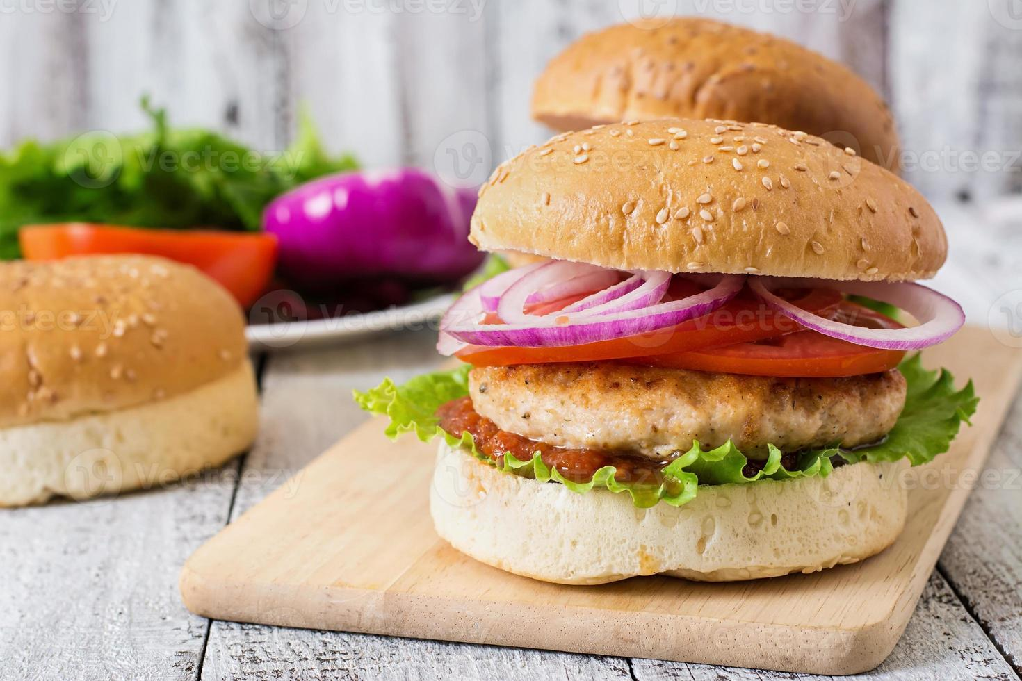 sanduíche com hambúrguer de frango, tomate, cebola roxa e alface foto