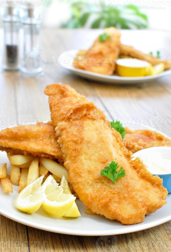 prato de peixe e batatas fritas em uma mesa de madeira foto