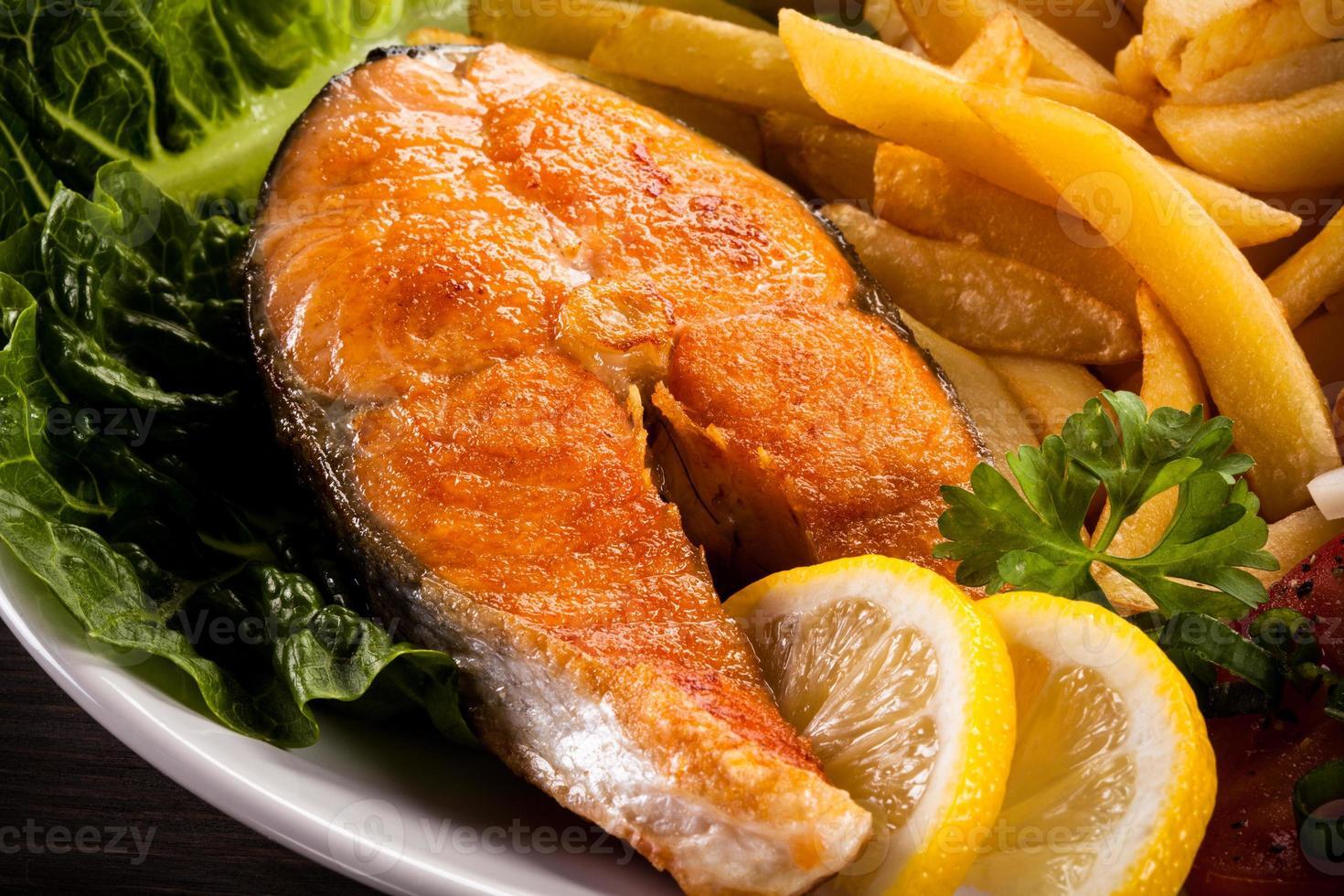 salmão assado, batata frita e legumes foto