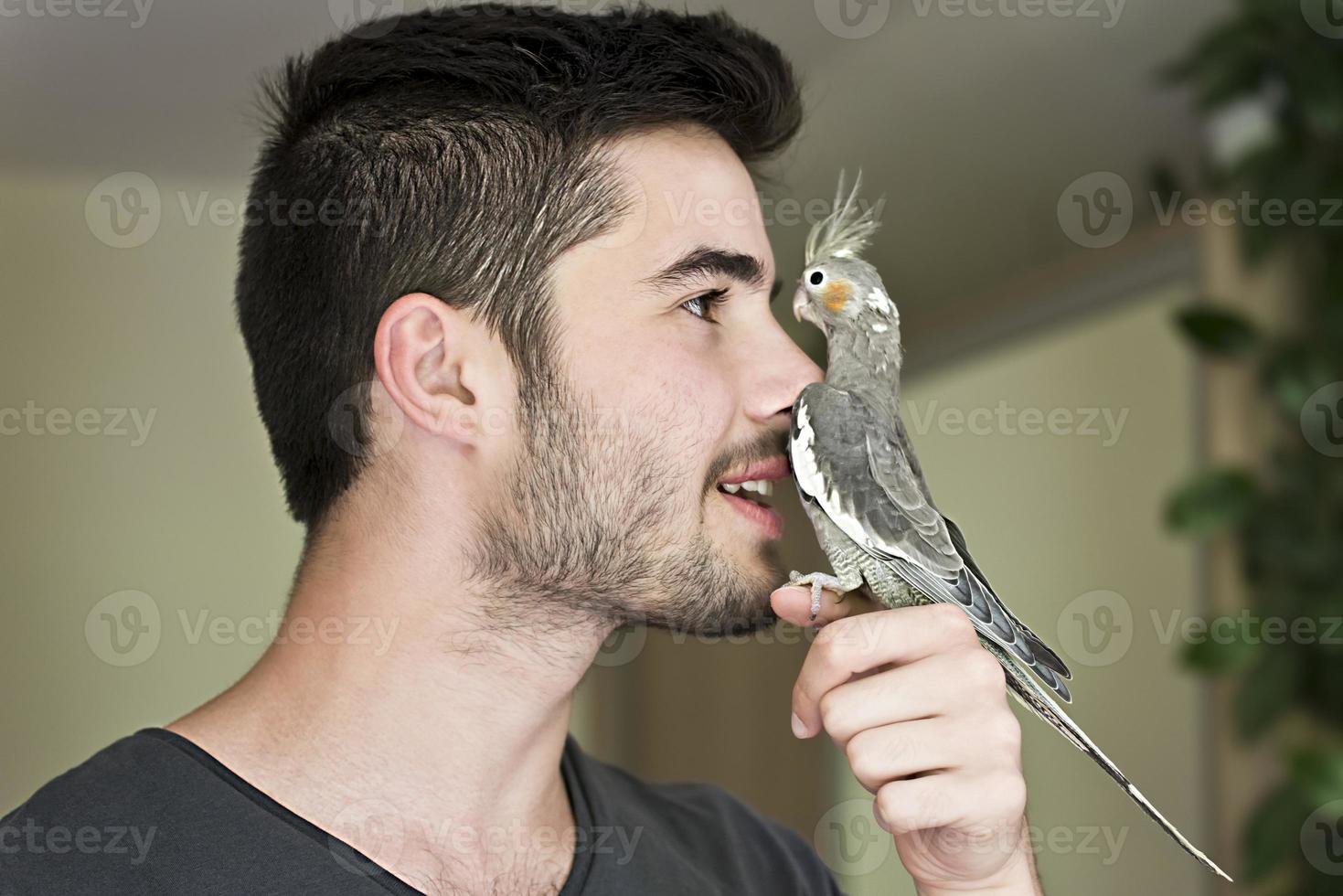 homem atraente, brincando com seu papagaio dentro de casa foto