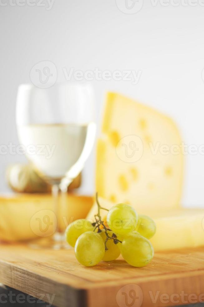 queijo e vinho em uma mesa de madeira foto