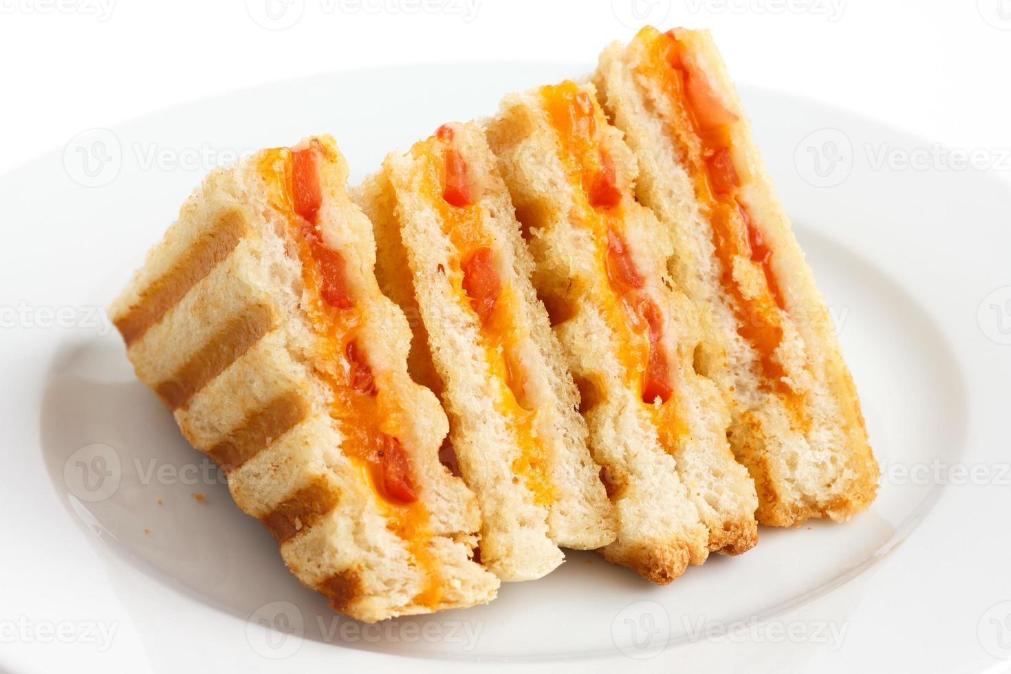clássico tomate e queijo torrado sanduíche no prato branco. foto
