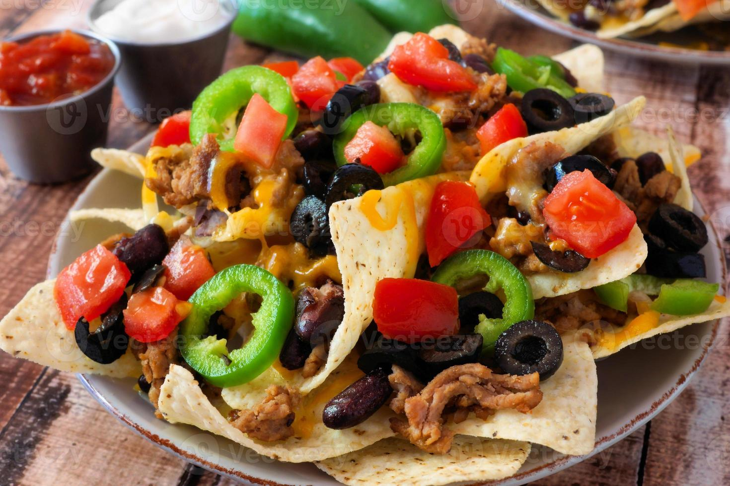 prato de nachos mexicanos picantes totalmente carregados foto