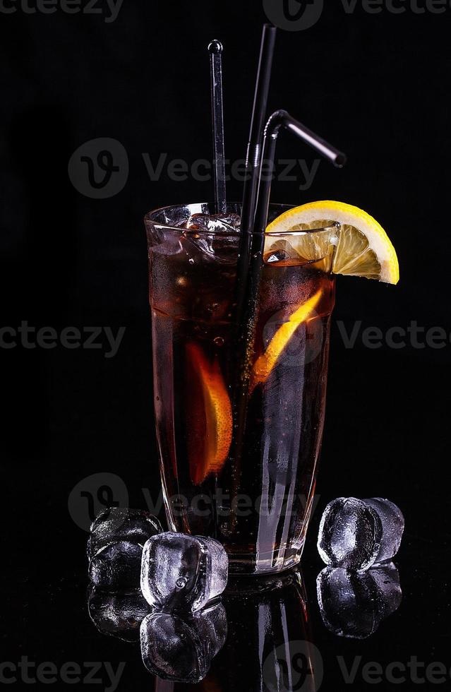 copo de coca-cola com gelo e limão. foto