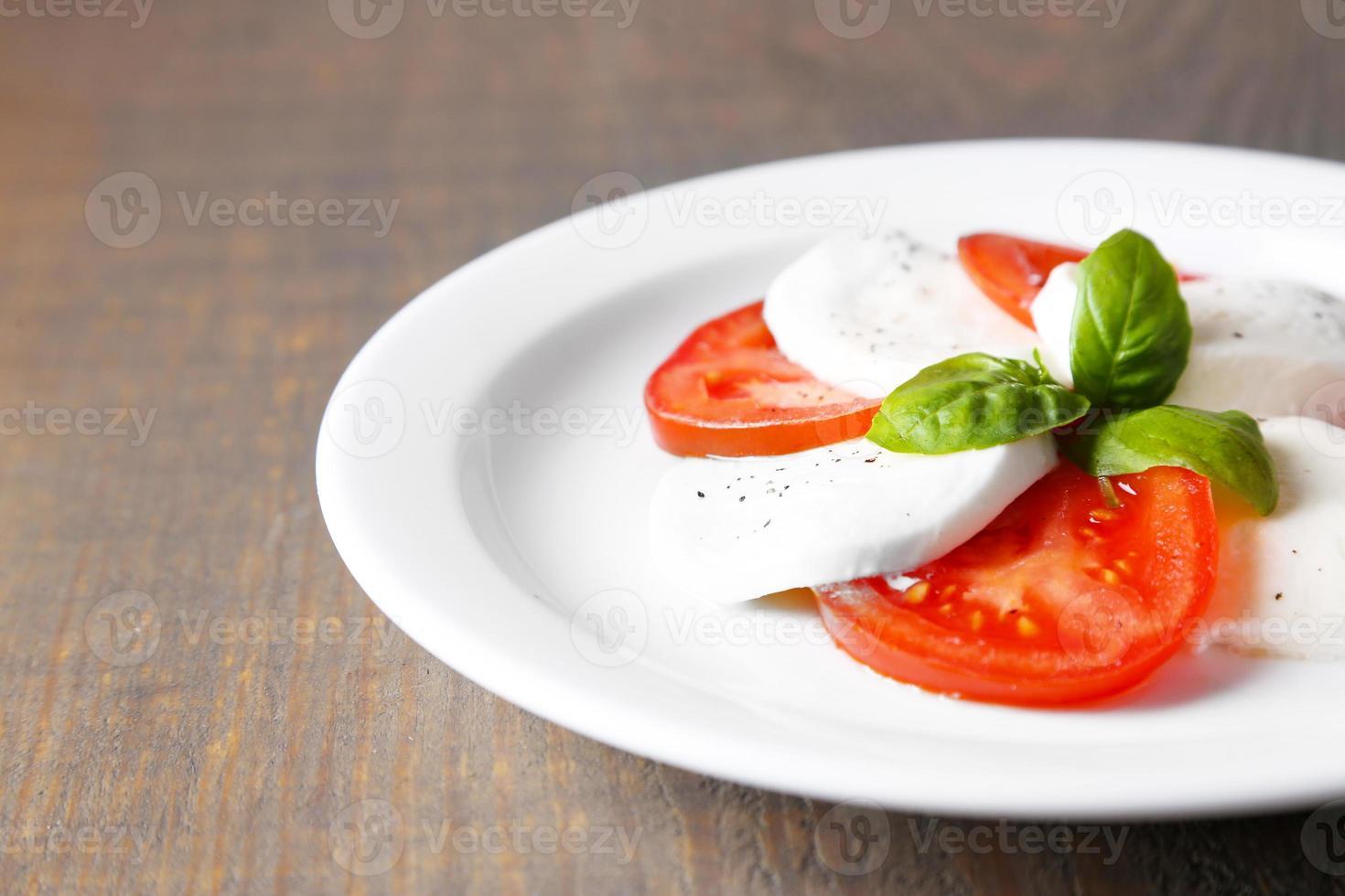 salada caprese com queijo mozarella, tomate e manjericão no prato foto