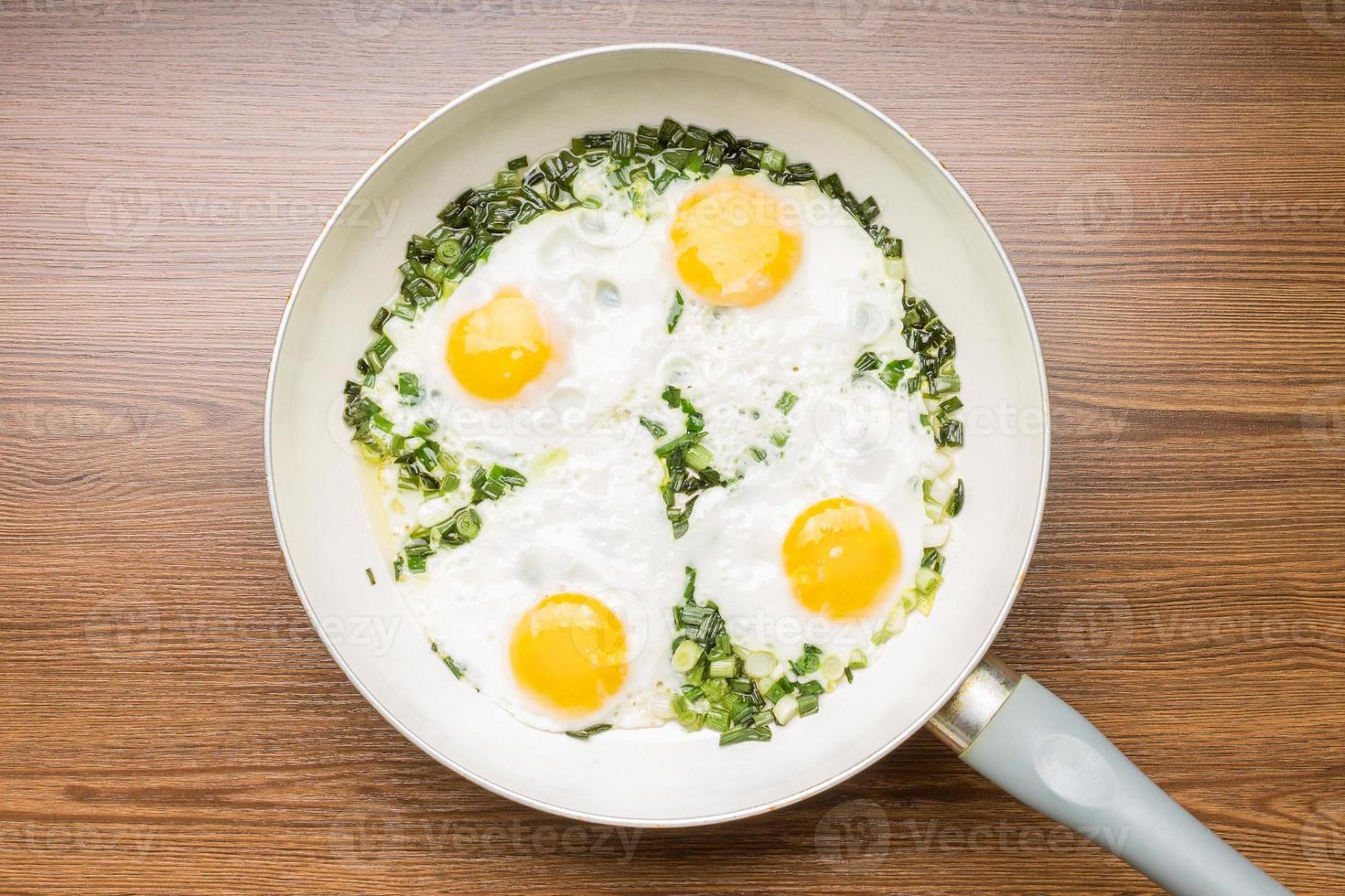 ovos fritos na frigideira com fundo de madeira foto