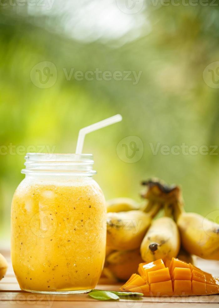 smoothies manga e banana em uma jarra de vidro foto