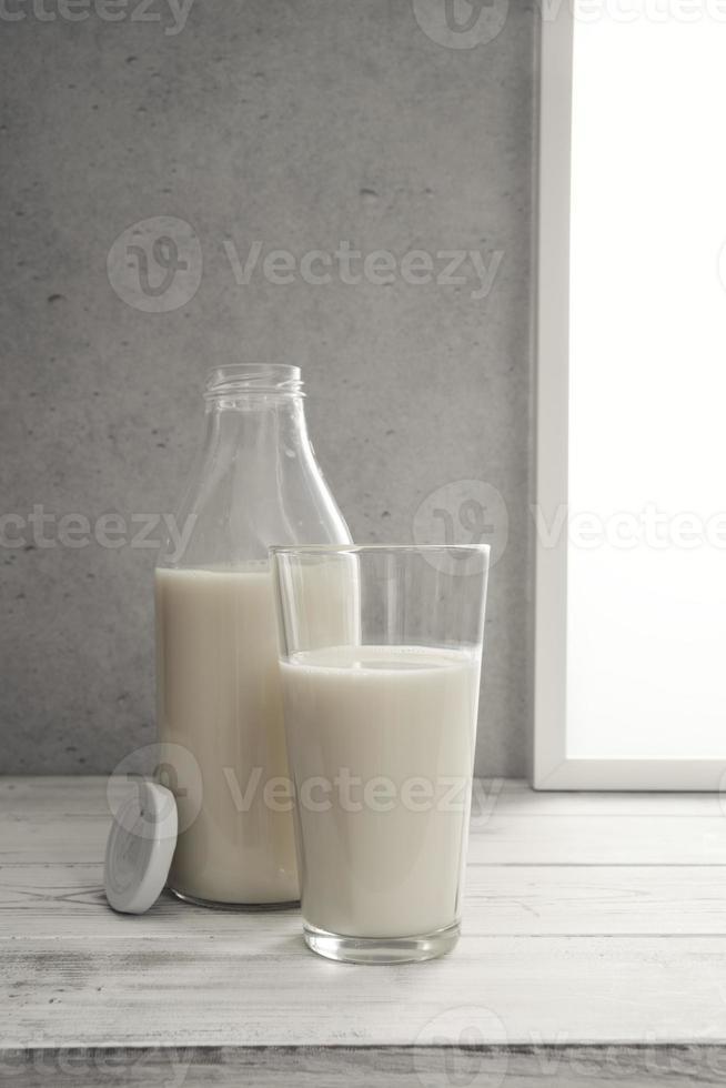 garrafa de leite e copo cheio de leite no peitoril da janela foto