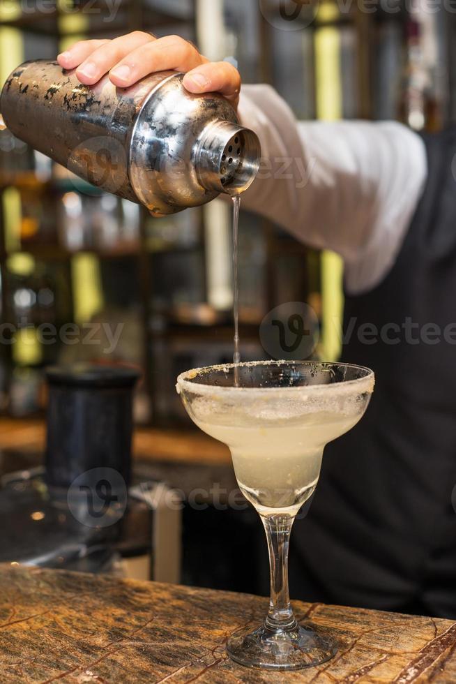 Braga no trabalho, preparando cocktails. derramando margarita em copo de coquetel. foto