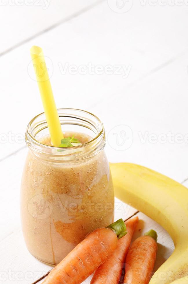 shake de cenoura e banana na mesa branca foto