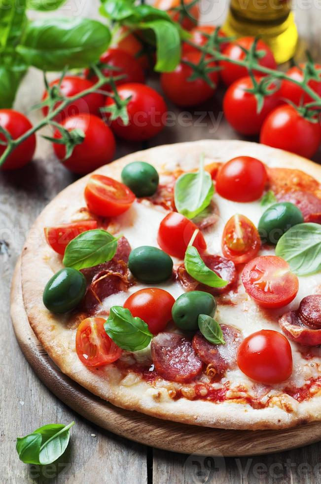 pizza quente italiana com salame, azeitona e tomate foto