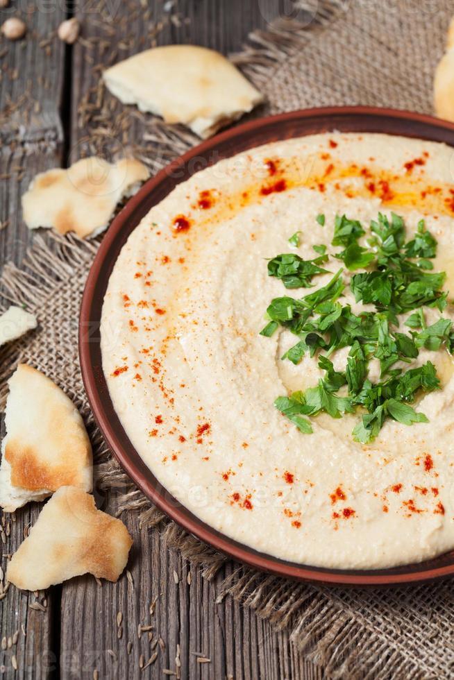hummus cremoso em prato rústico de barro, servido com pita, colorau foto