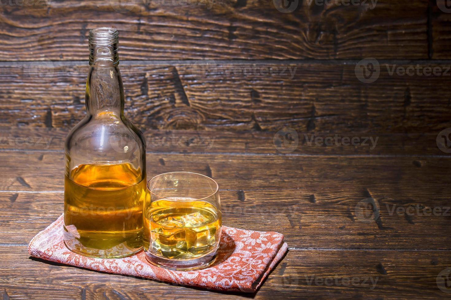 garrafa com um copo com uísque no guardanapo foto