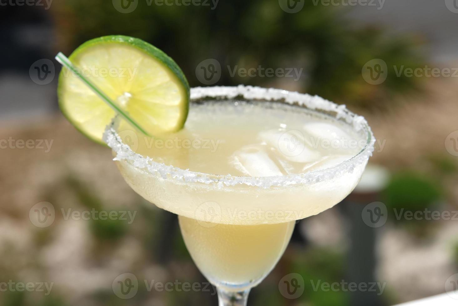 close-up de margarita com borda salgada e limão foto