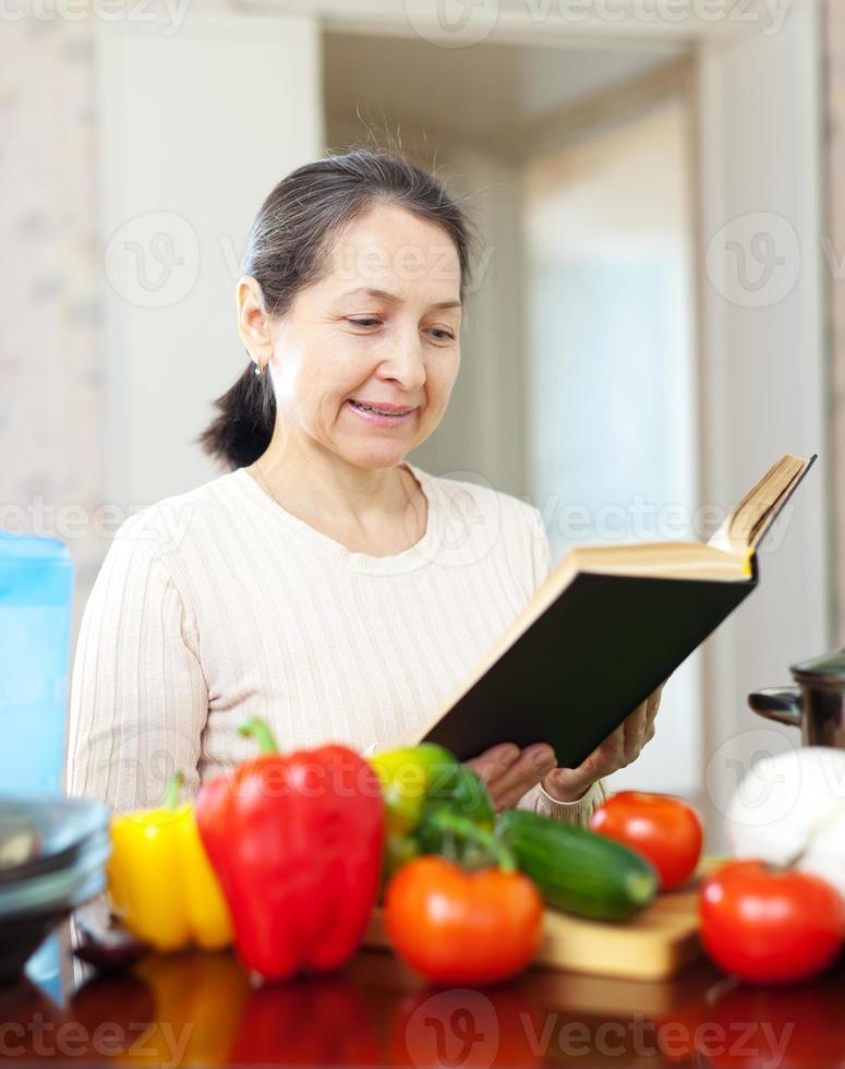 mulher lê livro de receitas para receita na cozinha foto