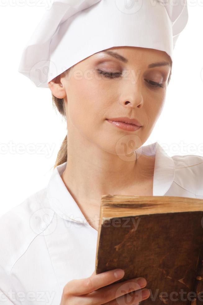 mulher cozinheira lendo livro de receitas foto