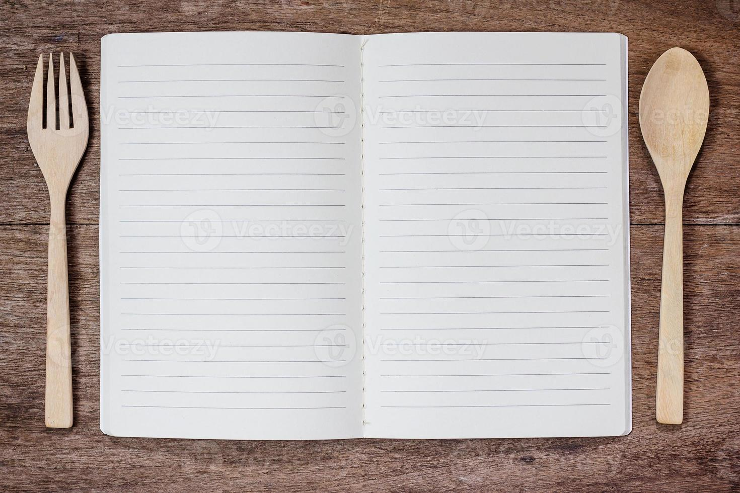 livro de receitas e colher, garfo na madeira foto