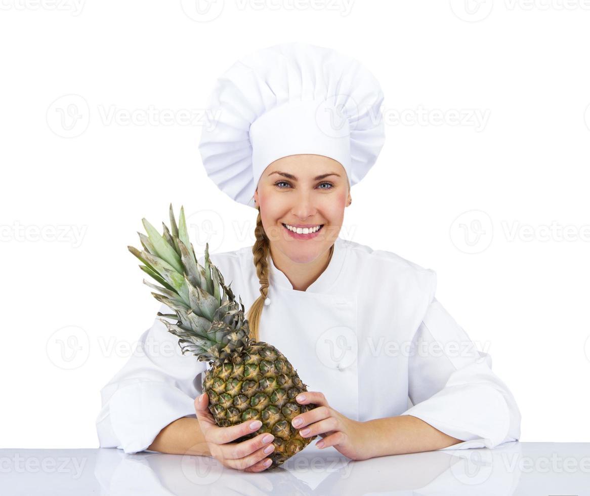 chef de mulher de uniforme. isolado no fundo branco com abacaxi foto
