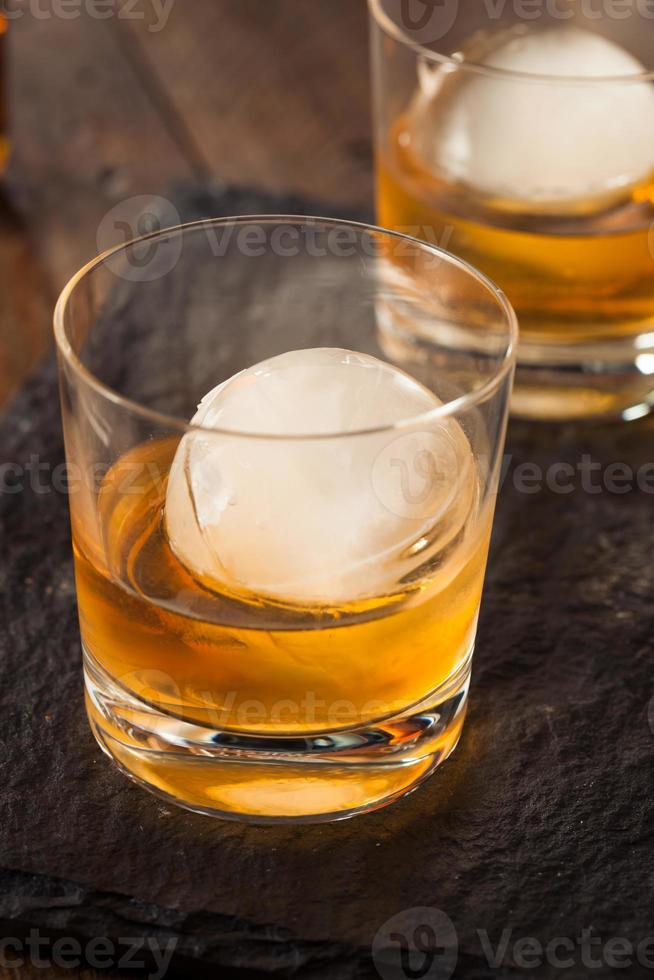 uísque de bourbon com um cubo de gelo de esfera foto