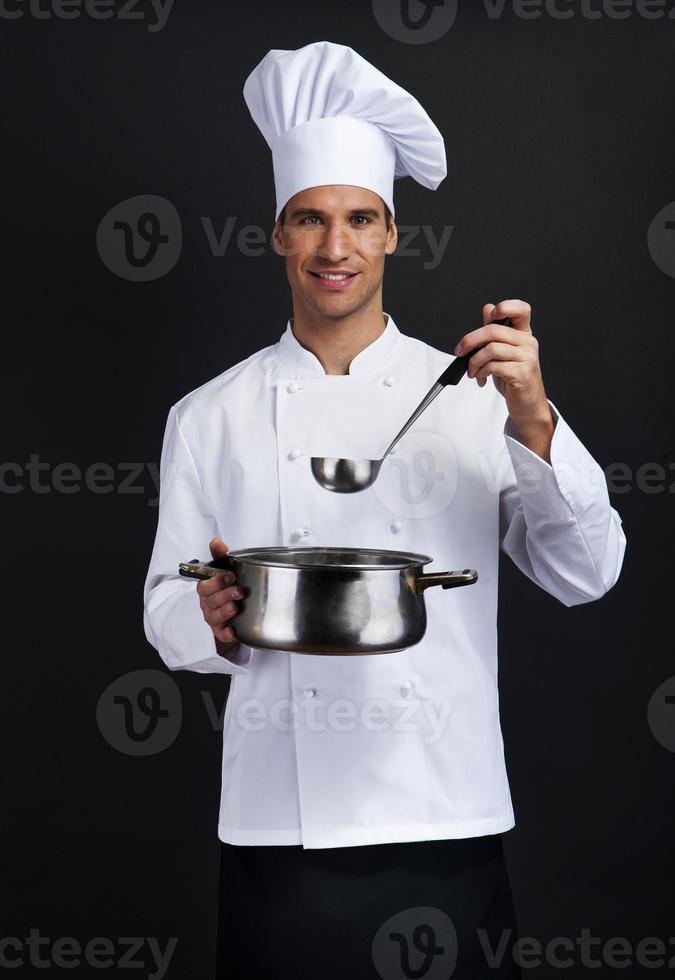chef cozinheiro contra o fundo escuro, sorrindo com a colher de chapéu holdinf foto