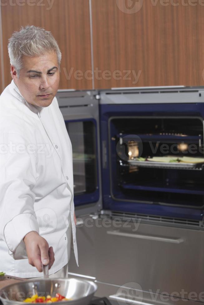 chef cozinhar legumes na panela de trabalho foto