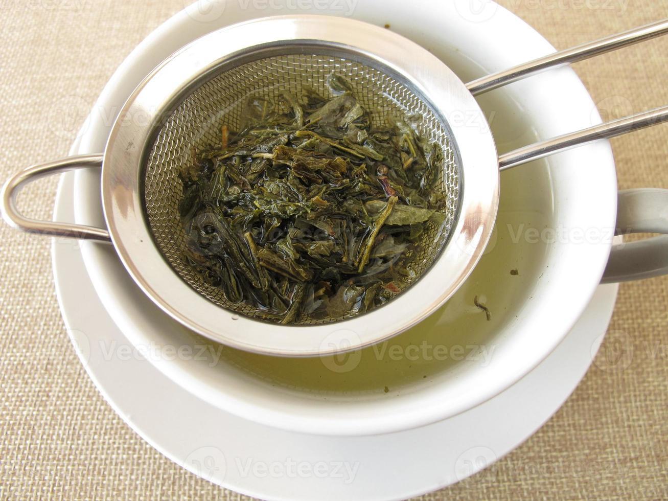 chá verde em coador de chá foto