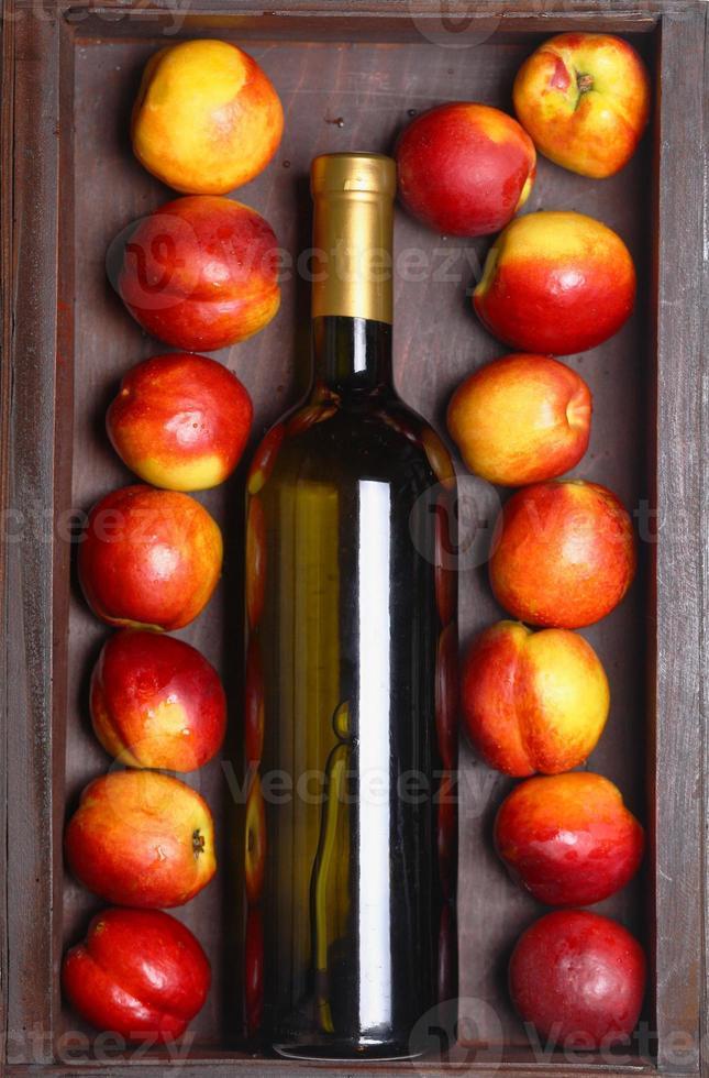 vinho branco e pêssegos foto