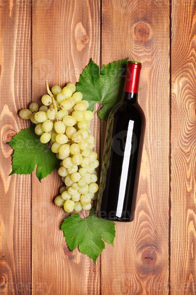garrafa de vinho tinto e cacho de uvas brancas foto