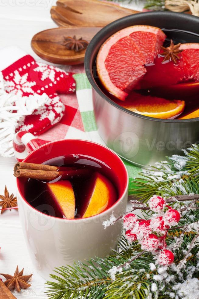 Natal mulled vinho na mesa de madeira com árvore do abeto foto